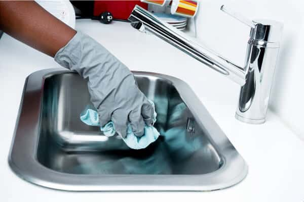 persona limpiando el fregadero con guantes